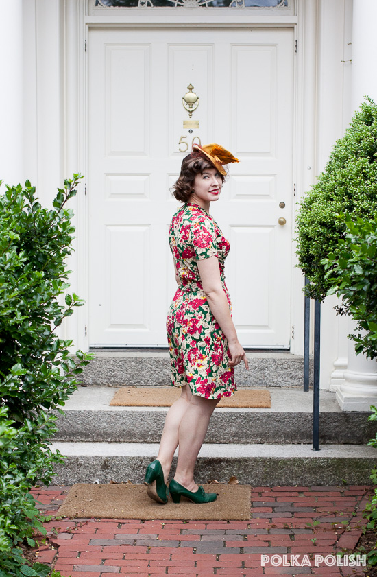 A bold 1940s floral jersey dress paired with a yellow tilt hat and green shoes