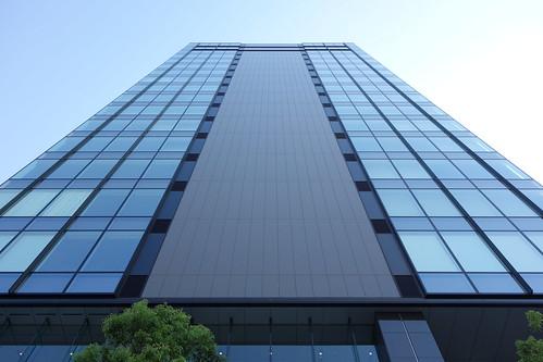"""Ueno_(2013_08_28)_1 オフィスビルディングの写真。 """"TIXTOWER UENO""""。 直下から見上げて撮影したもの。 ガラス張り。"""