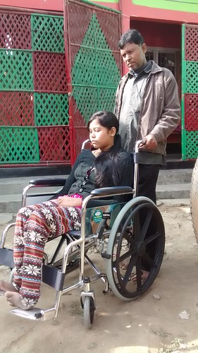 Rinki Begum, who is left physically handicapped in a bomb blast, being helped by her father Hussain Ali to move on a wheel chair