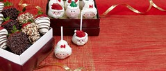 Santa Claus and other Christmas cake and brownie pops with dipper strawberries covered in chocolate chips and nuts on a red table with some ribbon