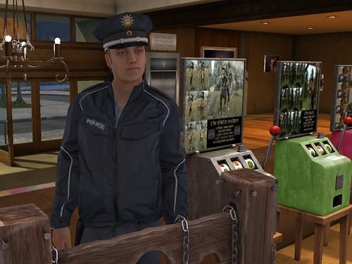 Image Description: Cop standing inside of a building.