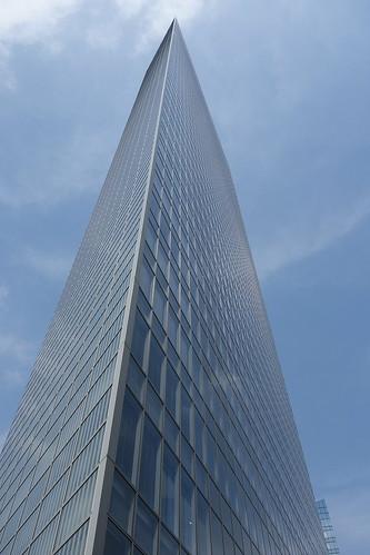 "Shimbashi_8 新橋で撮影した高層ビルディングの写真。 ""電通本社ビル""。 横側の直下から見上げる角度で撮影。 全面ガラス張り。 角は際立った鋭角である。"