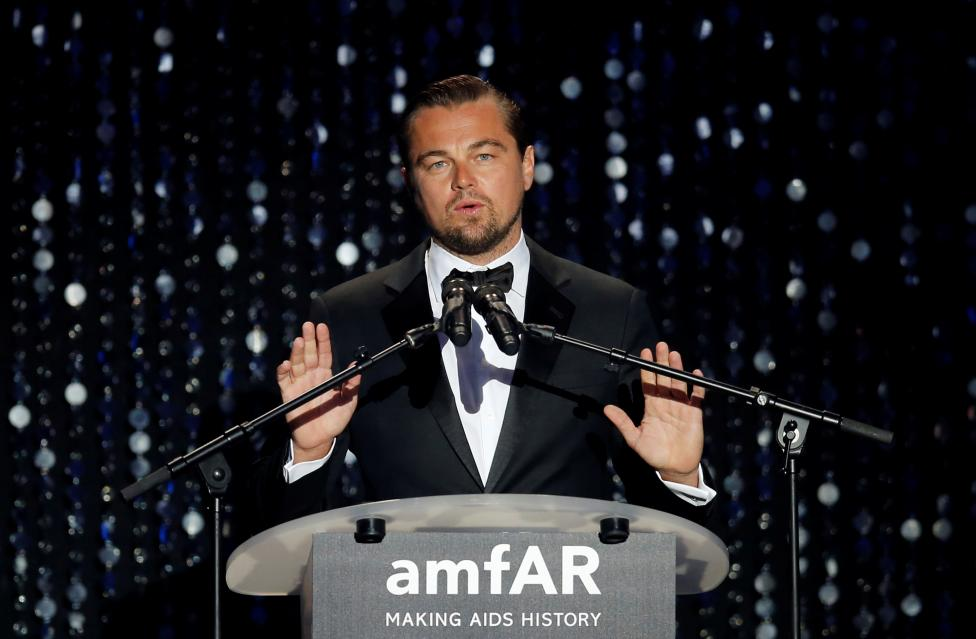 Actor Leonardo Di Caprio conducts an auction an auction during the amfAR's Cinema Against AIDS 2016 event during the 69th Cannes Film Festival in Antibes