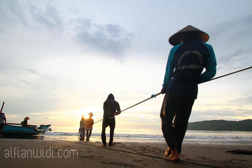 3.Nelayan menarik jaring dari laut.