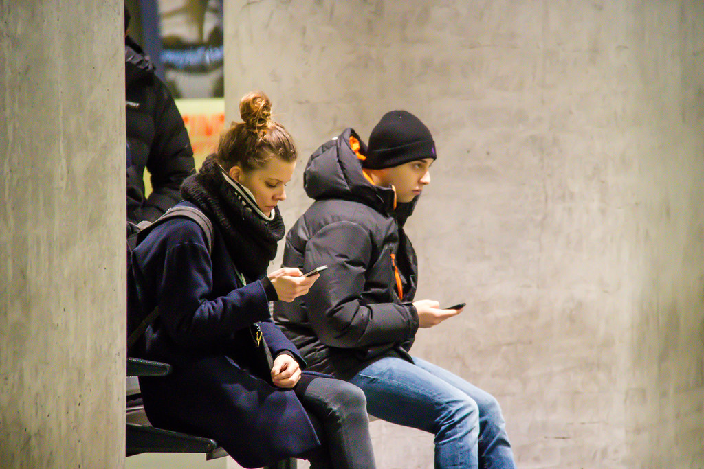 People with phones at the station - texting