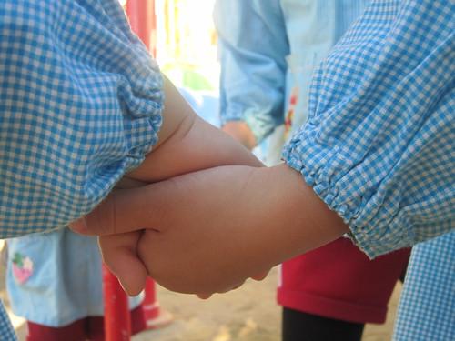 年少児の手をとる年長児