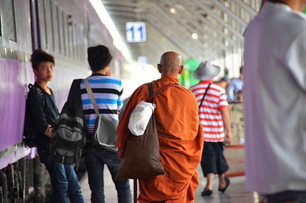 Monje budista caminando por una estación de trenes en Tailandia