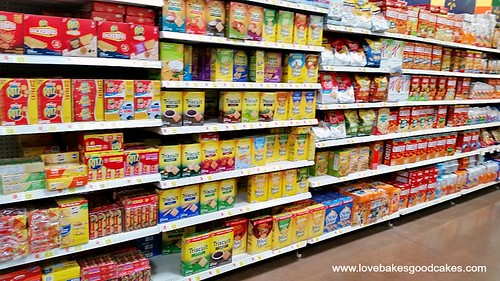 A grocery store isle with products on the store shelves.
