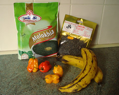 "Groceries arranged on a kitchen countertop with white tiles behind: a green plastic freezer packet labelled ""Molokhia"", showing a bowl of chopped dark green leaves; a gold plastic packet with a clear front window and small black beans inside, labelled ""Dried Iru""; two ripe plantains; and four scotch bonnet chillies, three yellow and one red."