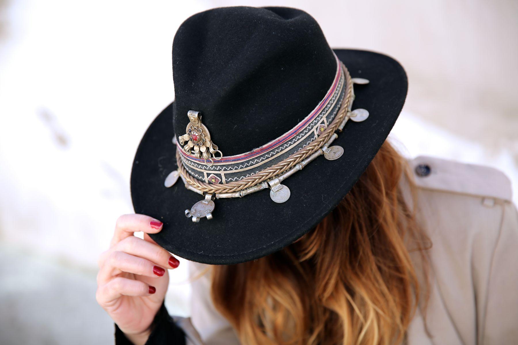 Look boho con sombrero, vestido negro, trench y botines camperos