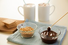 chocolate sauce in a bowl next to crushed graham crackers and two mugs of hot cocoa