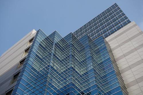"""Ikebukuro_5 池袋駅西口側で撮影した """"メトロポリタンプラザビル"""" の写真。 水平方向に段々になった縦長の青いガラス張りの部分がある。 ガラス面に水平方向の枠が映り込んで幾何学模様を浮かび上がらせている。"""