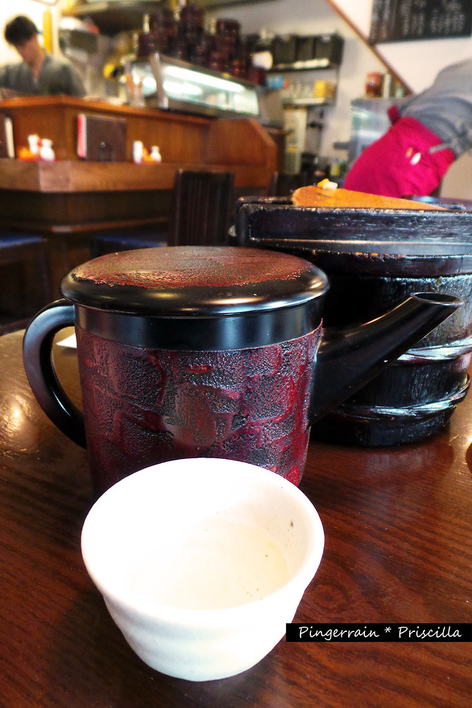 Broth soup in a lacquered jug and teacup bowl