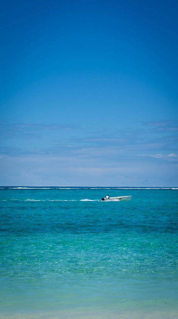 Paradis : Bateau Blanc ou Barque sur Océan Turquoise avec Ciel Bleu et Lagon de Rêve d'une Ile un Jour de Beau Soleil
