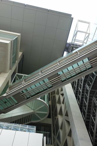 "Tokyo_24 東京都丸の内の ""東京国際フォーラム"" の写真。 見上げる角度で撮影したもの。 螺旋外階段と空中通路とコンクリート造りの格子状の巨大な柱が写っている。"