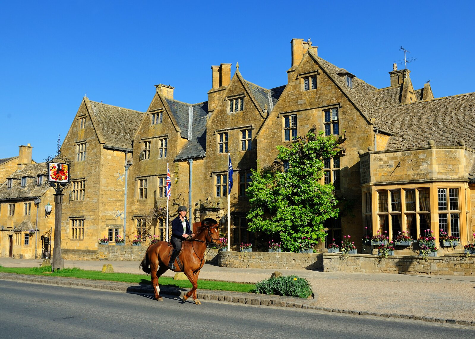 A rider passes in front of the Lygon Arms hotel in Broadway. Credit Saffron Blaze