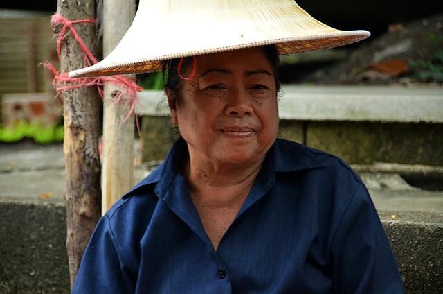 Señora con sombrero típico tailandés sonriendo a la cámara en Damnoen Saduak