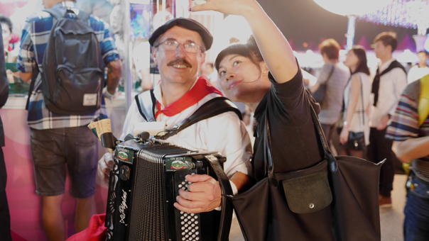 A reveller taking a selfie with accordionist at the Argentina Wine & Dine booth