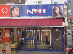 "A terraced shopfront with a sign above reading ""NASH Unisex Salon"".  A photo of a Black man with cropped hair and sharply-styled facial hair is on the left side of the sign, and a photo of a Black woman with straight hair flipped over one eye is on the right side.  The frontage is fully glazed, and the shop opposite is reflected in this, making it hard to see inside."