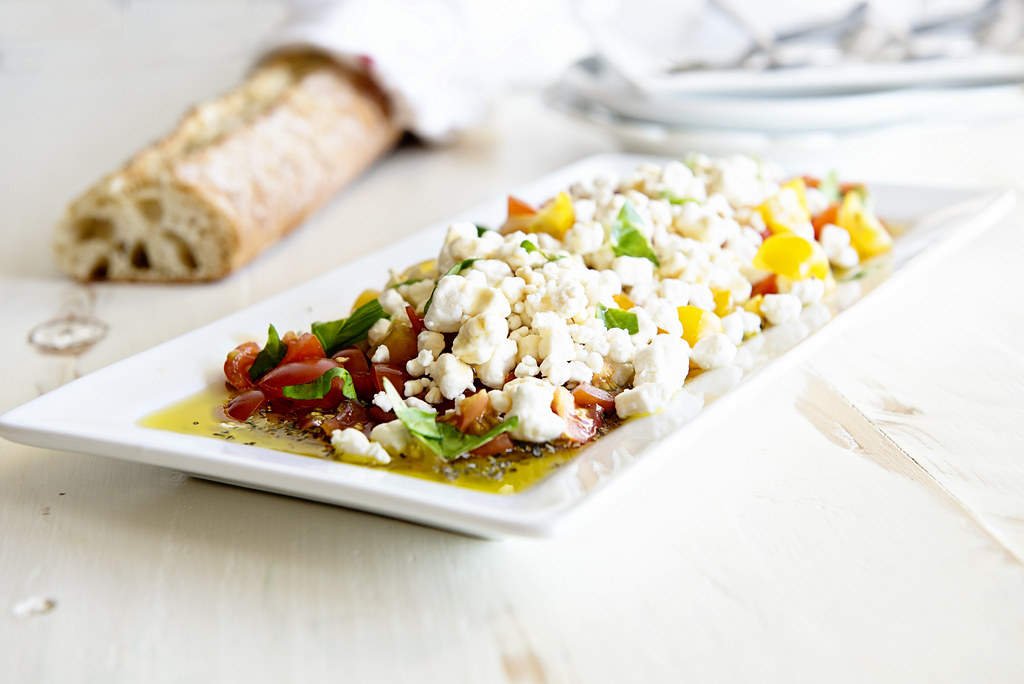 Goat cheese crumble appetizer with red and yellow cherry tomatoes basil leaves Italian seasoning, balsamic vinegar and honey on a tray next to a french bread baguette on a white table