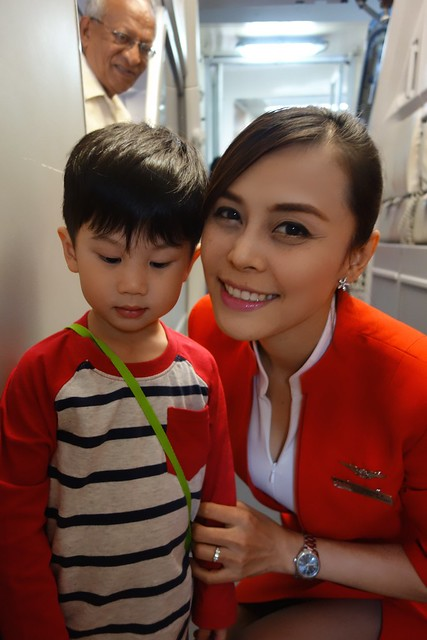 The shy boy who didn't dare to look up while pretty stewardess takes a picture with him.