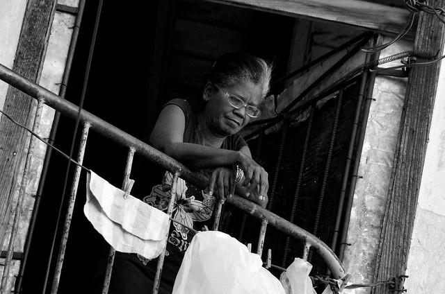 Señora apoyada en una barandilla construida con una valla de obra en La Habana