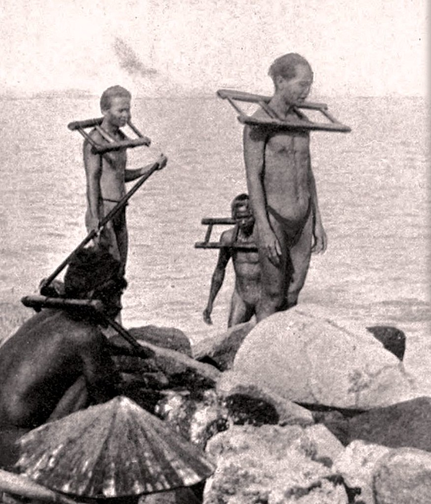 Nearly naked prisoners wearing the cangue work on a dike - Vietnam - ca 1910