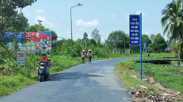 Banners and billboards lining the small road leading to Vi Thanh