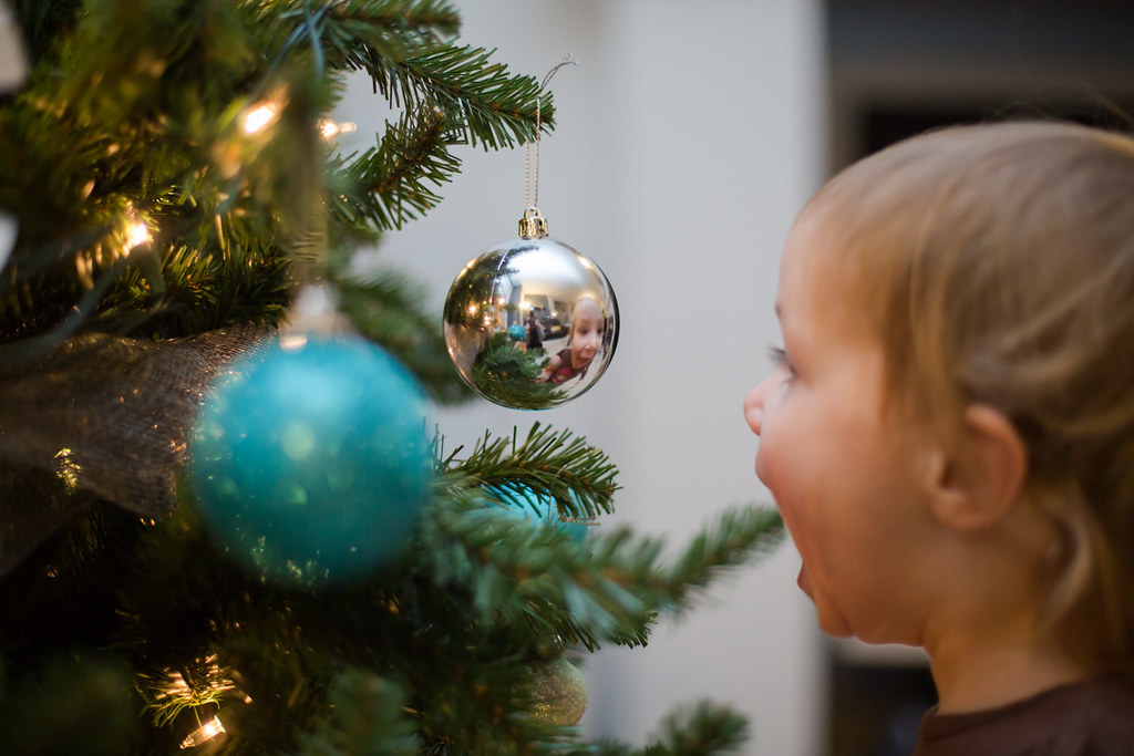 Child's image reflected in a Christmas ornament