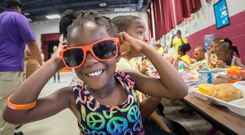 A smiling girl with orange glasses at lunch.