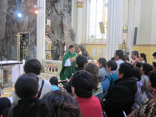 The priest blesses people with holy water after mass