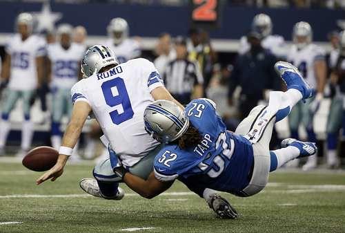 El defensivo Darryl Tapp (52), de Detroit, detiene al mariscal Tony Romo (9), de Dallas, en el juego realizado en Arlington, Texas, donde los Leones perdieron el partido tras ir arriba en los tres primeros periodos y parte del último Foto Ap