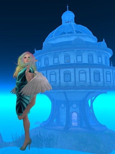 Image Description: Woman with rainbow hair and a teal outfit floating in midair before a mushroom shaped home on an island.