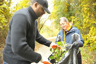Petty Officer 1st Class Darius Whiteside places a load of invasive English ivy into a garbage bag held by Petty Officer 3rd Class Cecelia Henry during a Coast Guard volunteer event at Paradise Creek Park in Portsmouth, Va., Thursday, Nov. 13, 2014. A group of Coast Guardsmen from the 5th District in Portsmouth removed the invasive species as part of volunteer effort led by the Elizabeth River Project. (U.S. Coast Guard photograph by Petty Officer 3rd Class Nate Littlejohn)