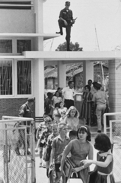 SAIGON 1964 - American children attending grade school, guarded by US troops after Viet Cong terrorist bombing
