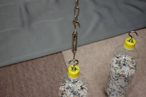 astronomical telescope_35 自作天体望遠鏡用の錘として使う金魚砂利入りのペットボトルの写真。キャップにボルト フックが付けられ、吊るされた鎖とターン バックル フック & フックで繋がっている。