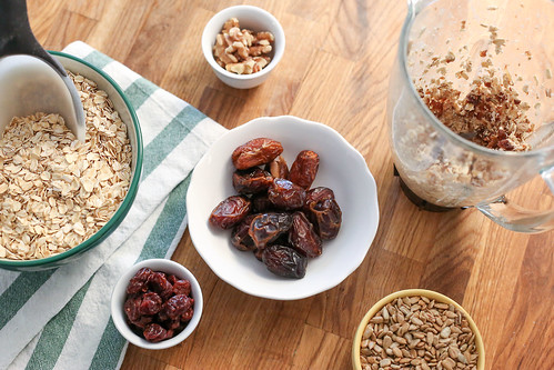 oatmeal dates seeds nuts in bowls with a measuring scoop and a pitcher on a wood table