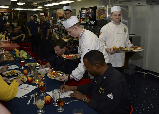 "RED SEA – Culinary Specialist 3rd Class Simon Riley, Culinary Specialist 3rd Class Eric Kapfhamer, and Culinary Specialist Seaman Aaron Simon present entrées to the senior chain of command aboard amphibious assault ship USS Makin Island (LHD 8), who participated as judges for Makin Island's first ""Iron Chef"" competition."