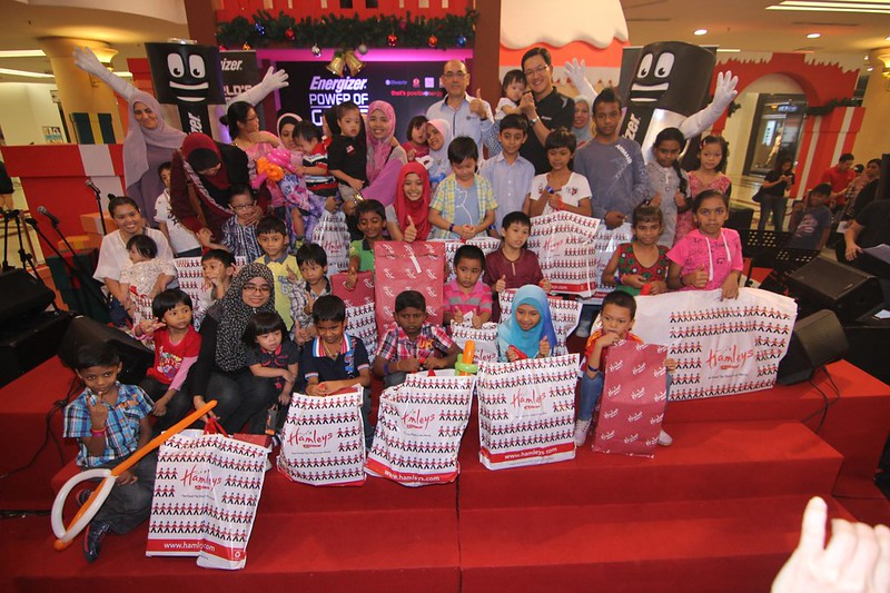 Mr Tan and Mr Harris have a photo taken with the children after they've received their gifts