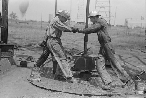 1939. Roughnecks leaning on the wrench to tighten the joint in the pipe from oil well in Oklahoma.