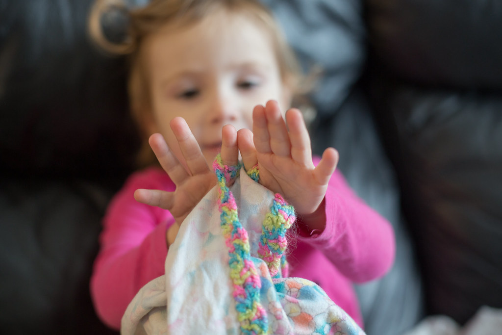 Toddler girl holding a special blanket