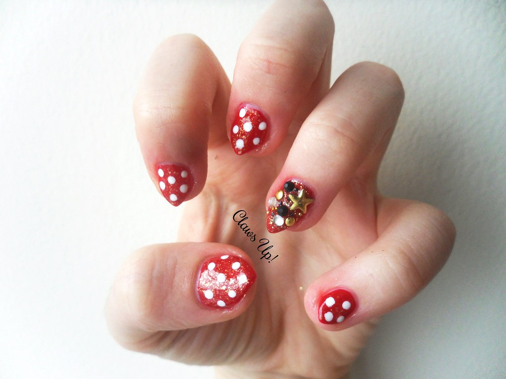 Red manicure with white polka dots and gold embellishments