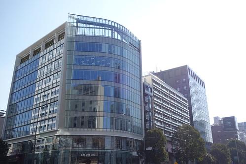 """Aoyama_8 青山にある高層ビルディングを撮影した写真。 """"LOUNGE by Francfranc(ラウンジ バイ フランフラン)""""。 交差点の対角側から撮影したもの。 全面ガラス張りで前面は曲面の壁面。 下部はモノトーンの絵による装飾が施されている。"""