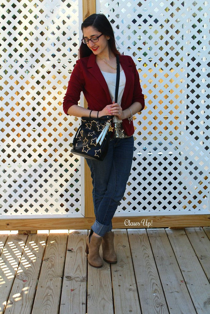 Betsey Johnson star bucket bag, red blazer, gold sequin top, and beige booties.