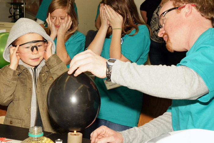 Participants in last year's Discover E event brace themselves while studying the fracture mechanics of an exploding balloon.