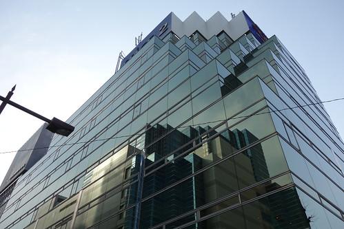 "Ikebukuro_7 池袋駅西口側で撮影した ""東武アネックス"" の写真。 全面が青いガラス張りである。 建物の上部の角が段々になっている。 ガラス面に ""メトロポリタンプラザビル"" が映り込んでいる。"