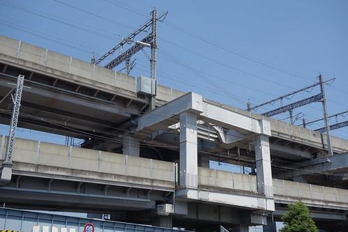 Omiya_5 高架の鉄道写真。 鋼鉄の橋脚とコンクリートの橋桁。 鉄のトラス構造の電柱とトラスビーム。 電線。