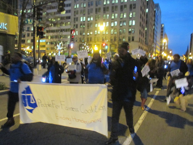 Advocates march in the street at night carrying a banner requesting an end to homelessness.  Photo by Elizabeth Falcon