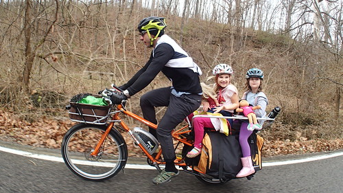 Girls with dolls on a cargo bike