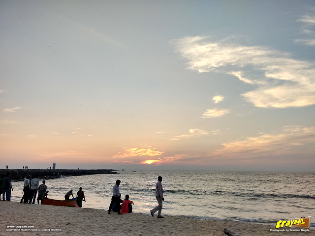 Fishermen parking their boat, and people watching the sunset on an evening in Panambur Beach, Mangalore, Mangaluru, Dakshina Kannada, Karnataka, India